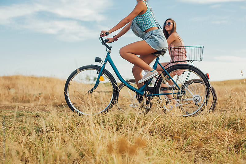 Two Girls Riding Bicycles Together by Lumina for Stocksy United