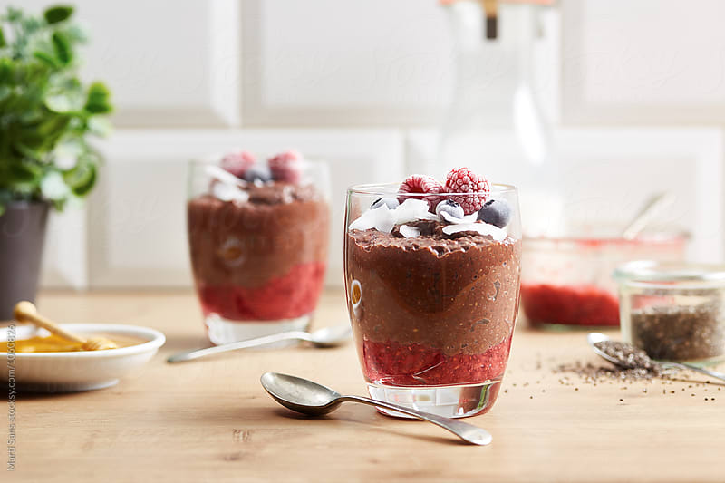 Delicious chia chocolate pudding with jam and coconut flakes and berries on top by Martí Sans for Stocksy United