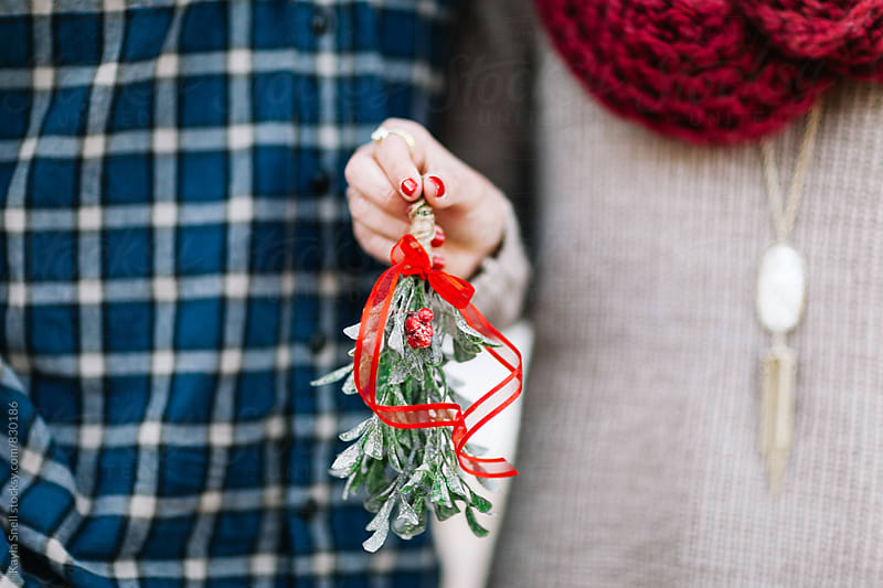 Christmas couple holding Mistletoe by Kayla Snell for Stocksy United