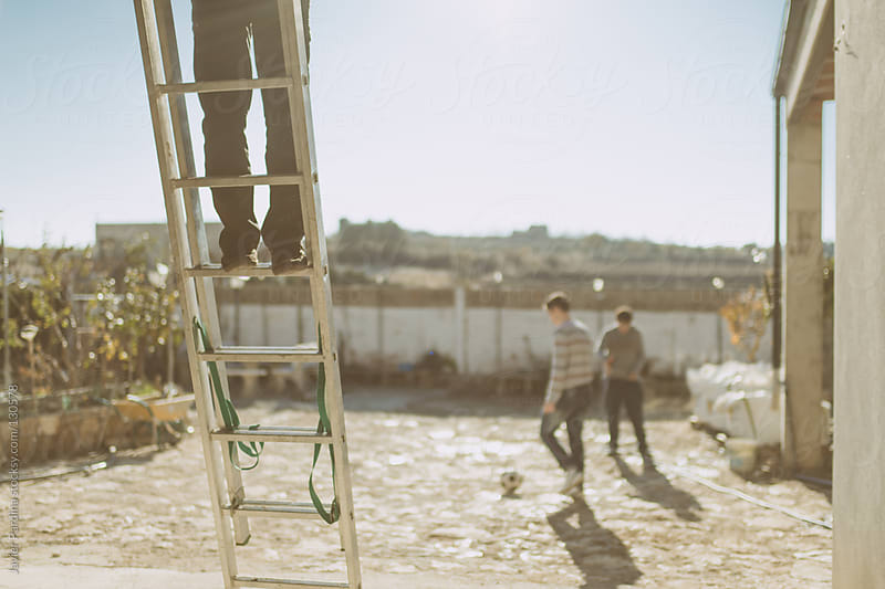 Young people play football while another works by Javier Pardina for Stocksy United