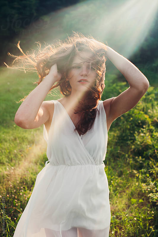 Sun rays across a girl in flowy white dress outdoors by paff for Stocksy United