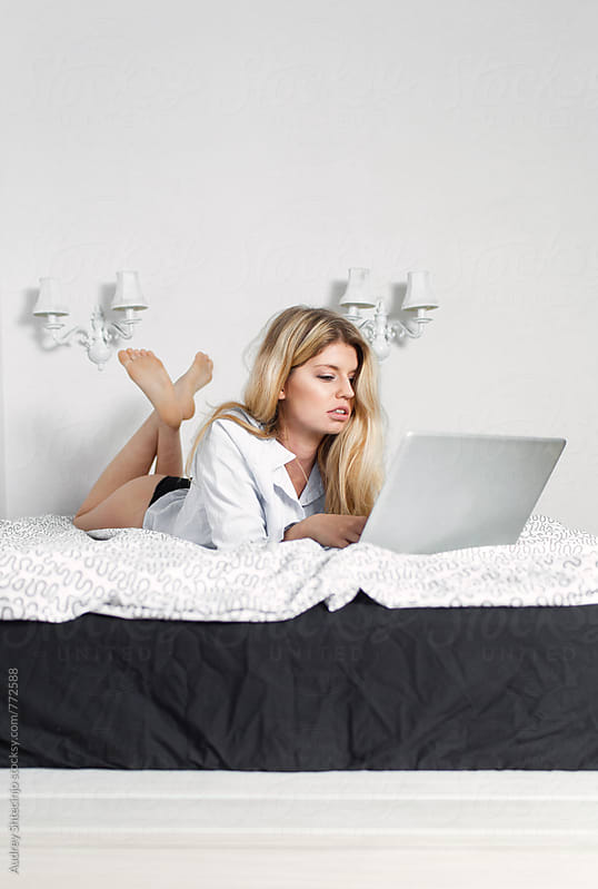 Young sensual blonde female on laptop in her bed  by Marko Milanovic for Stocksy United