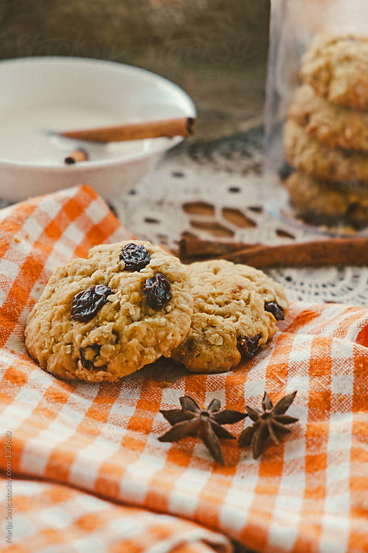 Oat cookies and milk with cinnamon served on wooden table. by Marija Savic for Stocksy United