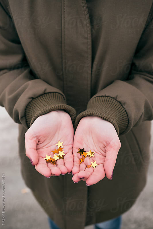 Close-up of hands with golden decorative stars by Danil Nevsky for Stocksy United