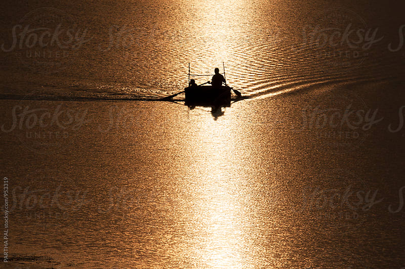 Two Person with floating vessel in a lake at evening time by PARTHA PAL for Stocksy United