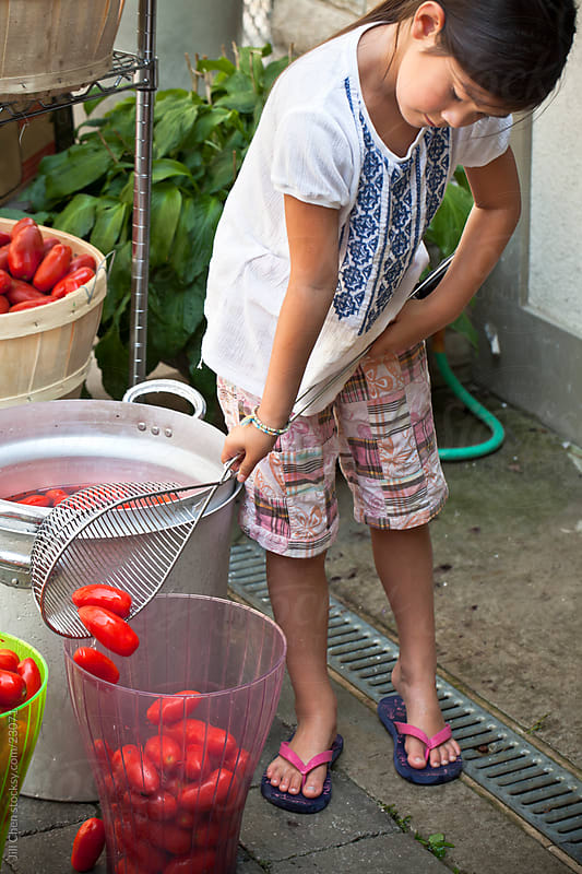 Straining Tomatoes by Jill Chen for Stocksy United