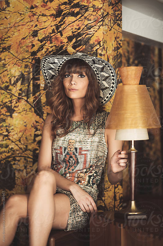 A young woman sitting against a forest wallpaper looking at camera by Ania Boniecka for Stocksy United