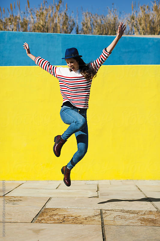 Happy young woman jumping in front of yellow background.  by BONNINSTUDIO for Stocksy United