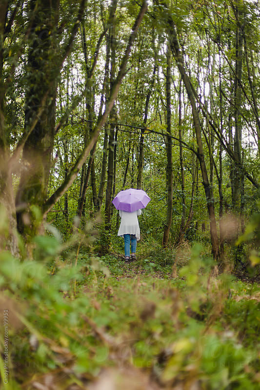 Woman from the back holding a purple umbrella walking in the woods by Cindy Prins for Stocksy United