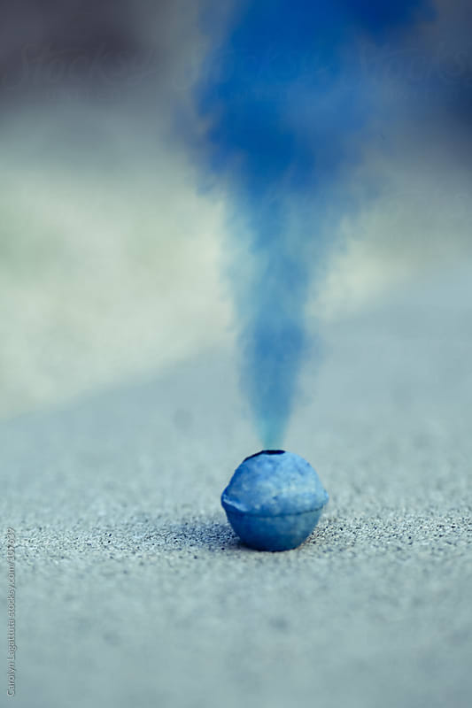 Smoke bomb with blue smoke pouring out by Carolyn Lagattuta for Stocksy United