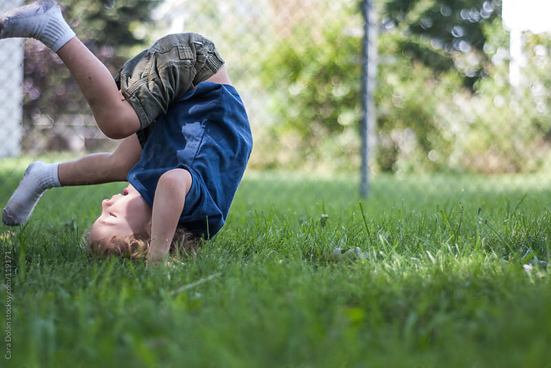 Young boy is in mid-somersault while playing outside in his yard by Cara Dolan for Stocksy United