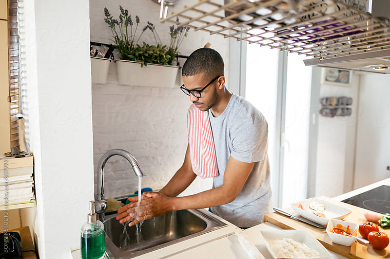 Latin man washing hands in the kitchen. by BONNINSTUDIO for Stocksy United
