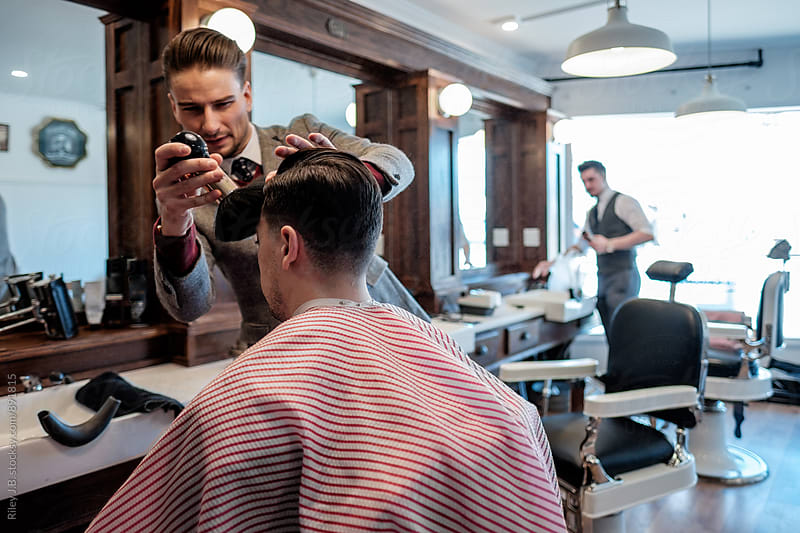 A gentleman barber brushes away hair from a client's forehead during a haircut. by Riley J.B. for Stocksy United