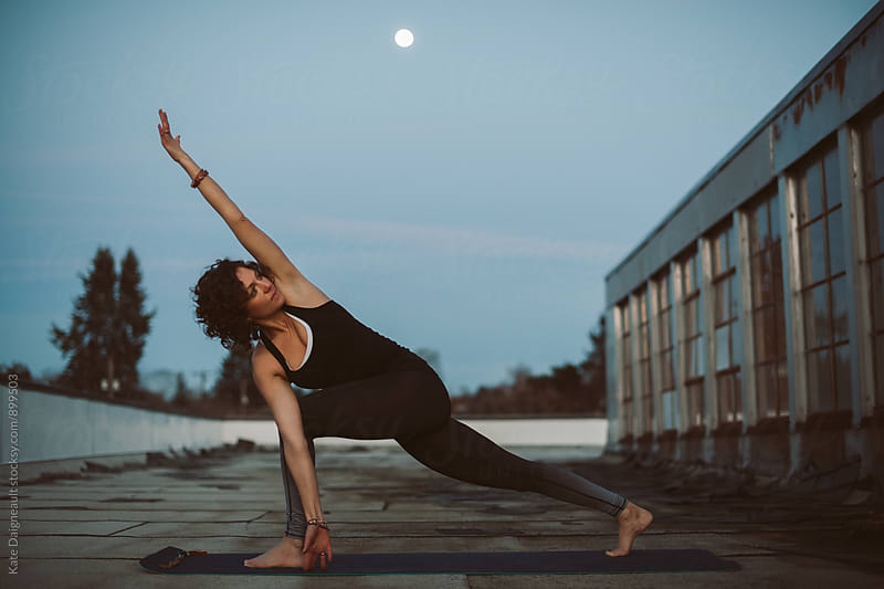 woman doing yoga on city rooftop at dusk. by Kate Daigneault for Stocksy United