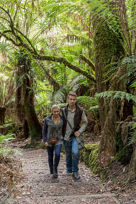 Young couple walking along a bush track by Ben Ryan for Stocksy United