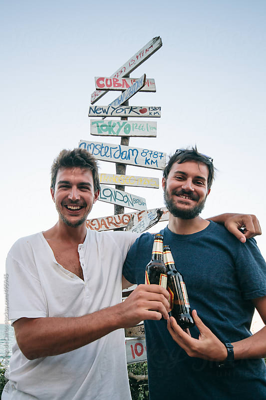Two young men friends toasting beers next to a signpost with directions and distance to various countries by Alejandro Moreno de Carlos for Stocksy United