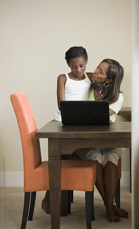 Mother and daughter (8-9) using laptop at home by Andersen Ross Photography for Stocksy United