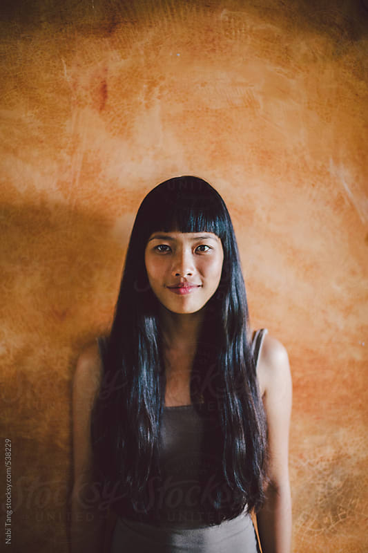 Asian young woman portrait smiling in front of yellow wall by Nabi Tang for Stocksy United