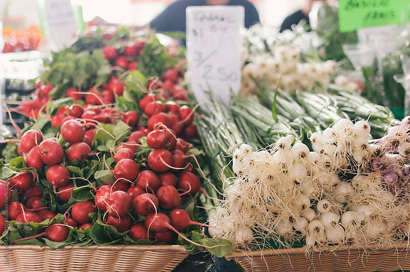 Green onions and radishes for sale at an outdoor market by Deirdre Malfatto for Stocksy United
