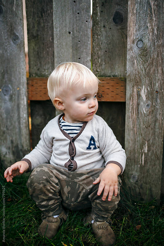 Toddler Boy Sits by an old Fence by Amanda Voelker for Stocksy United