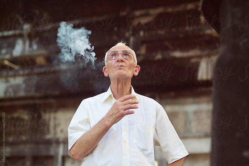 old man smoking in old factory by Marija Anicic for Stocksy United