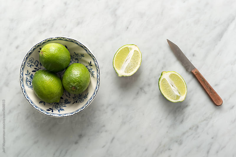 Limes on Marble Counter with Knife by Jeff Wasserman for Stocksy United