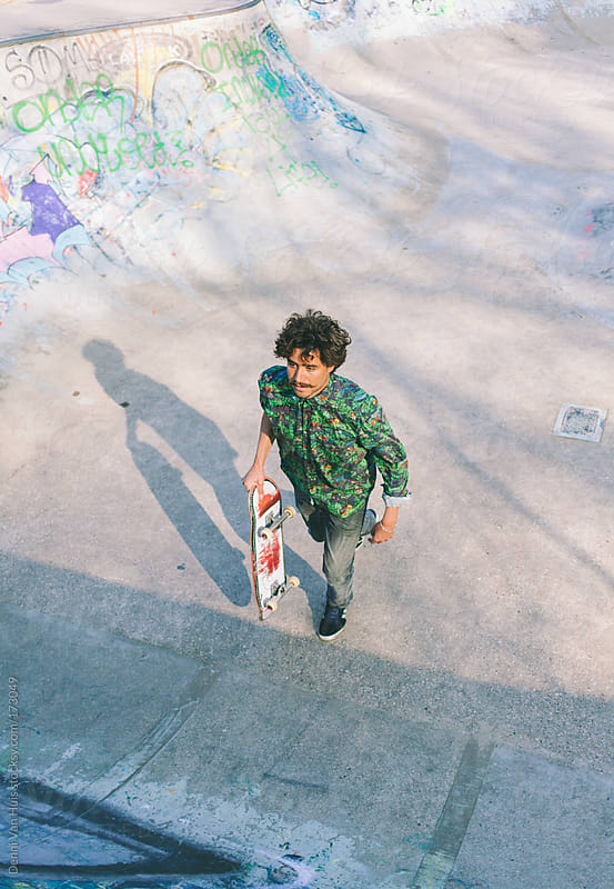 Young stylish man running up the ramp in skatepark by Denni Van Huis for Stocksy United