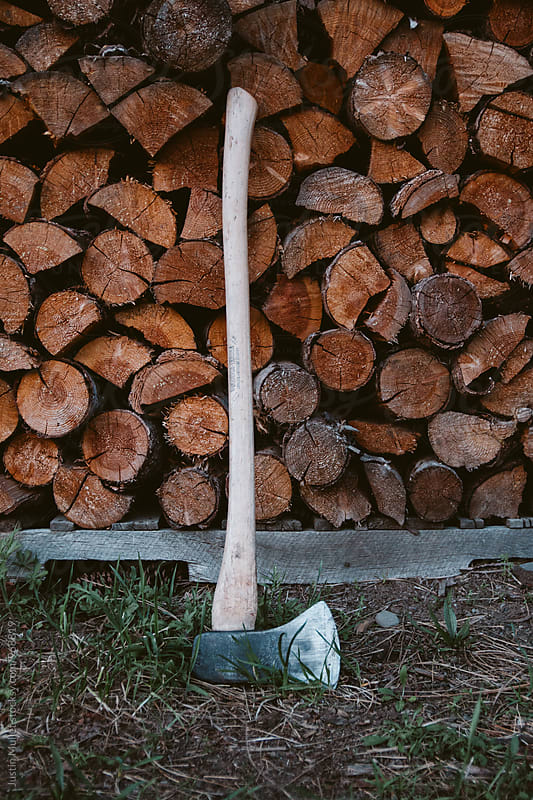 Wooden handled ax standing against a woodstack by Justin Mullet for Stocksy United