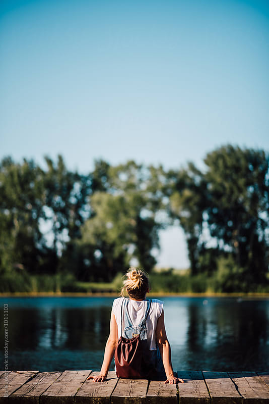 Woman sitting on the dock by the lake by Boris Jovanovic for Stocksy United