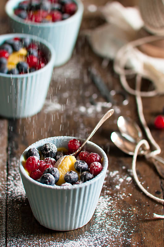 custard with currants and blueberries with icing sugar sprinkgling by Laura Adani for Stocksy United