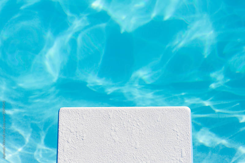 Dive in: View of the end of a diving board and pool water by Amanda Worrall for Stocksy United