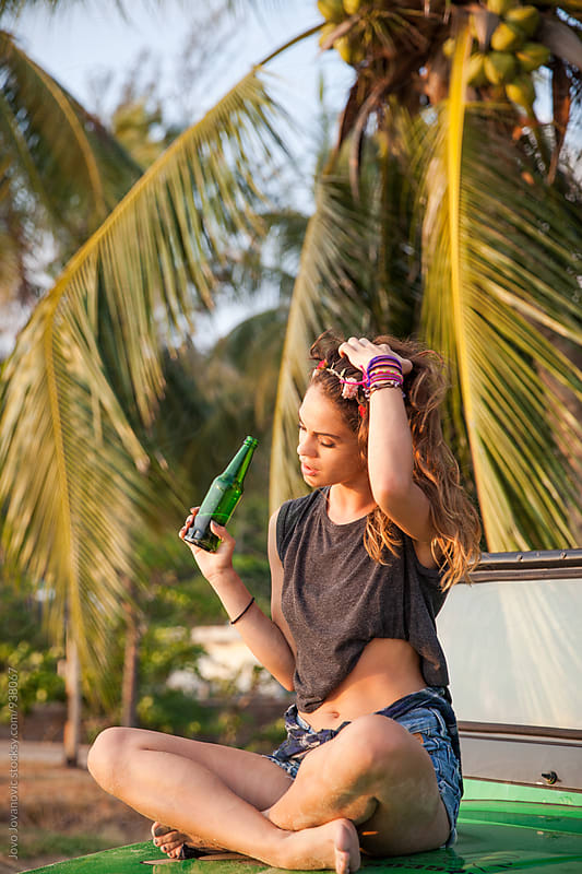 Beautiful woman drinking beer at the beach by Jovo Jovanovic for Stocksy United