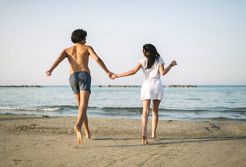 Happy young couple having fun on the beach by GIC for Stocksy United