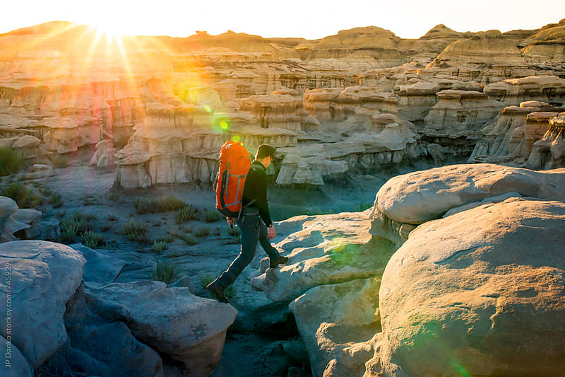 Backpacker Hiking Across Hoodoos in Bisti Badlands Wilderness Area New Mexico at Sunrise by JP Danko for Stocksy United