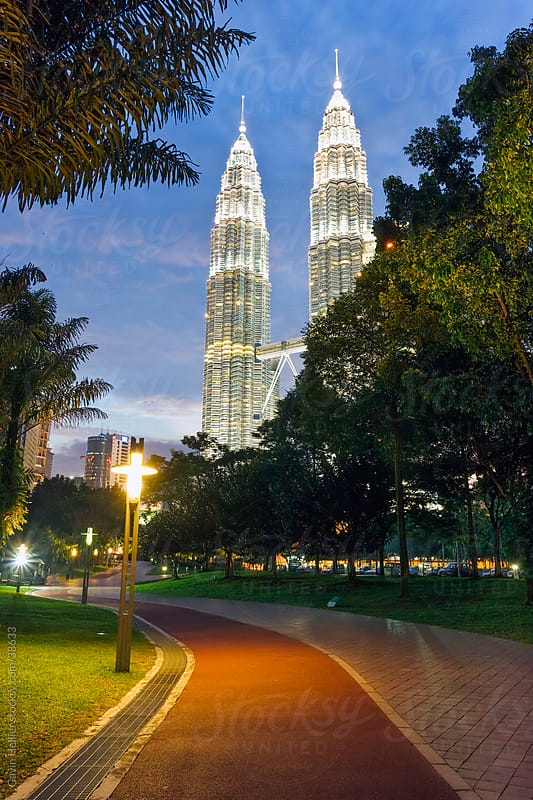 Asia, Malaysia, Selangor State, Kuala Lumpur, KLCC - Kuala Lumpur City Centre - urban development which includes the KLCC park, convention and shopping centre and the iconic 88 storey steel-clad Petronas Towers - illuminated at dusk by Gavin Hellier for Stocksy United