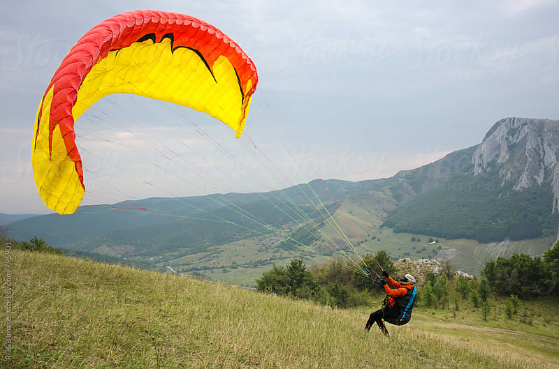 Paraglider raising his canopy to take flight by RG&B Images for Stocksy United