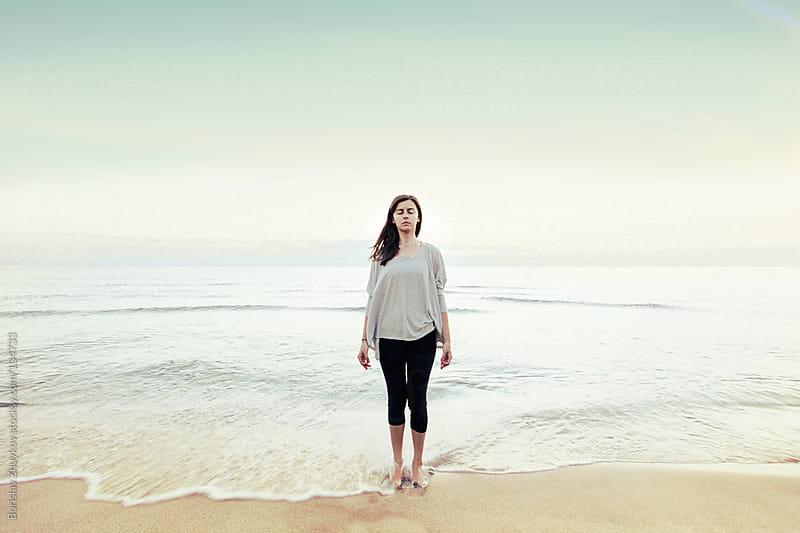 Woman meditating on the beach early in the morning by Borislav Zhuykov for Stocksy United