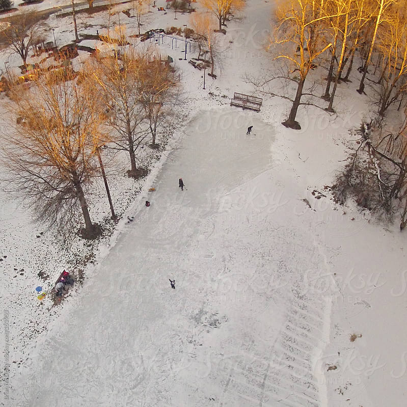 Overhead view of ice skaters playing hocket on local pond by Brian McEntire for Stocksy United