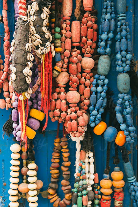 Close up of Moroccan necklaces and beads hanging against a blue doorway by Maresa Smith for Stocksy United