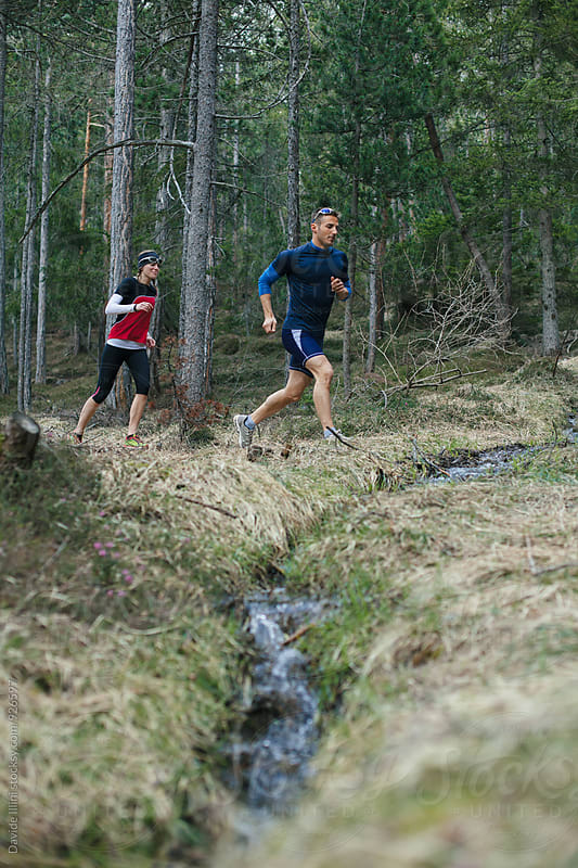 Two people running together in the forest by Davide Illini for Stocksy United