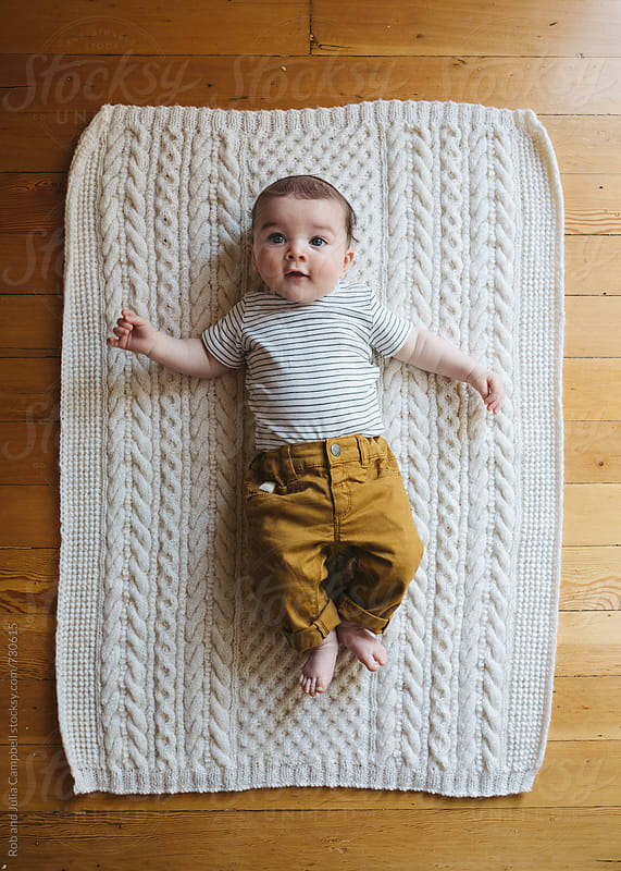 Cute young baby lying on blanket on floor by Rob and Julia Campbell for Stocksy United