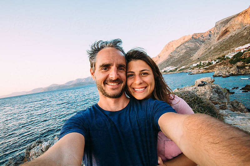 Happy couple taking a selfie on a beach in Kalymnos, Greece by Micky Wiswedel for Stocksy United
