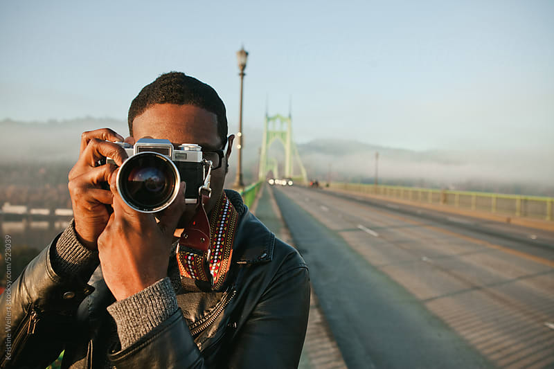 Portrait of a man taking photos with a vintage film camera by Kristine Weilert for Stocksy United