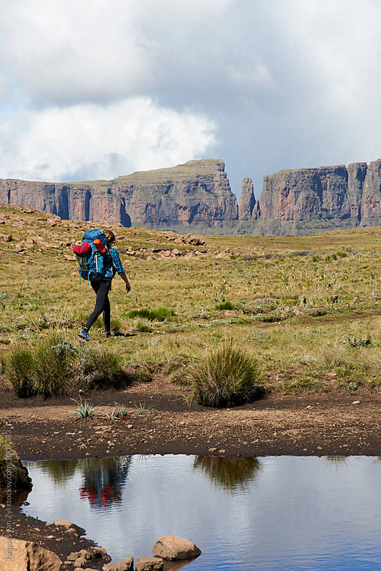female hiker with her back pack hiking through a grass field surrounded by mountains. by Jacques van Zyl for Stocksy United