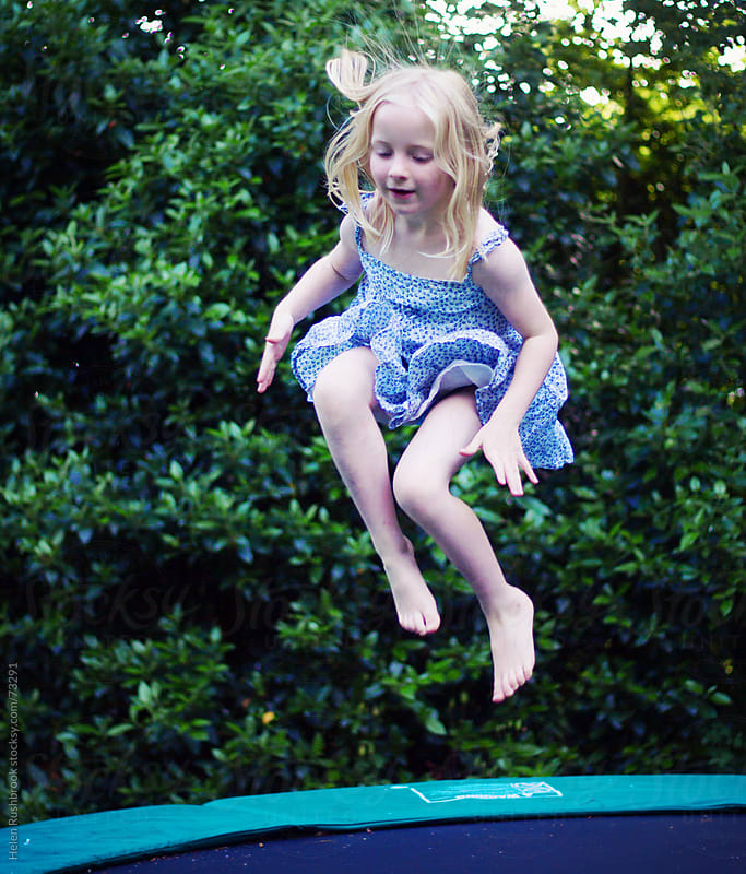 A little girl bouncing on a trampoline by Helen Rushbrook for Stocksy United