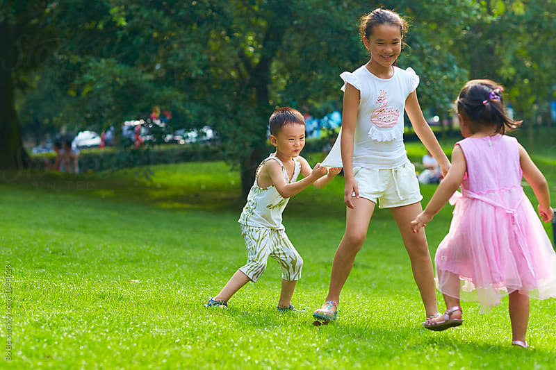 three children playing in the park by Bo Bo for Stocksy United