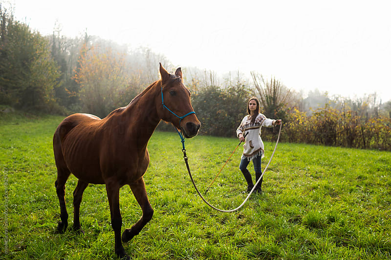Woman doing exercises of Natural Horsemanship with her horse by michela ravasio for Stocksy United