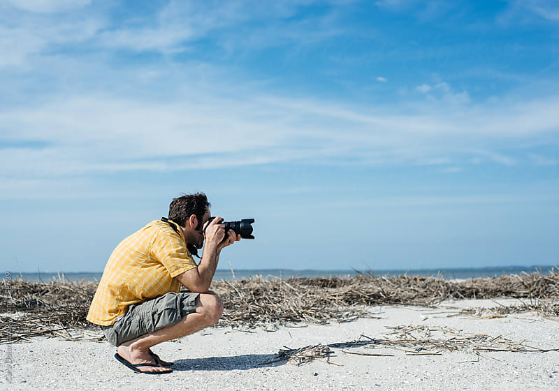 Man on a beach takes a photo with a digital SLR camera by Cara Dolan for Stocksy United