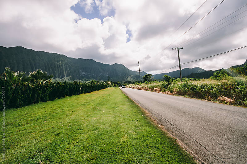 Road and moutains on green tropical setting by Alejandro Moreno de Carlos for Stocksy United