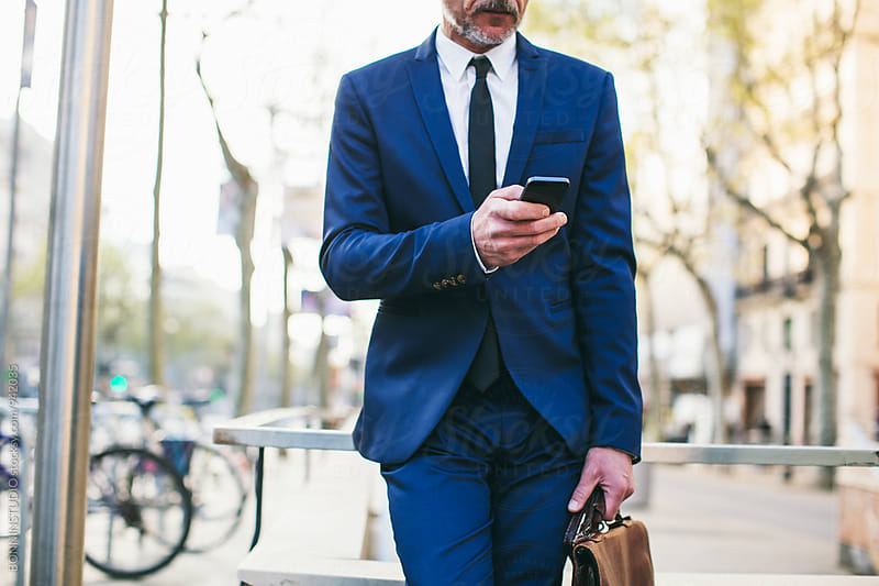 Closeup of a businessman walking on the street using phone. by BONNINSTUDIO for Stocksy United